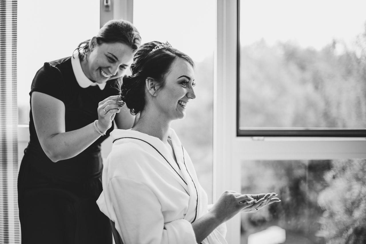 Die Visagistin bereitet die Haare der Braut für die Hochzeit im Hotel Darstein vor