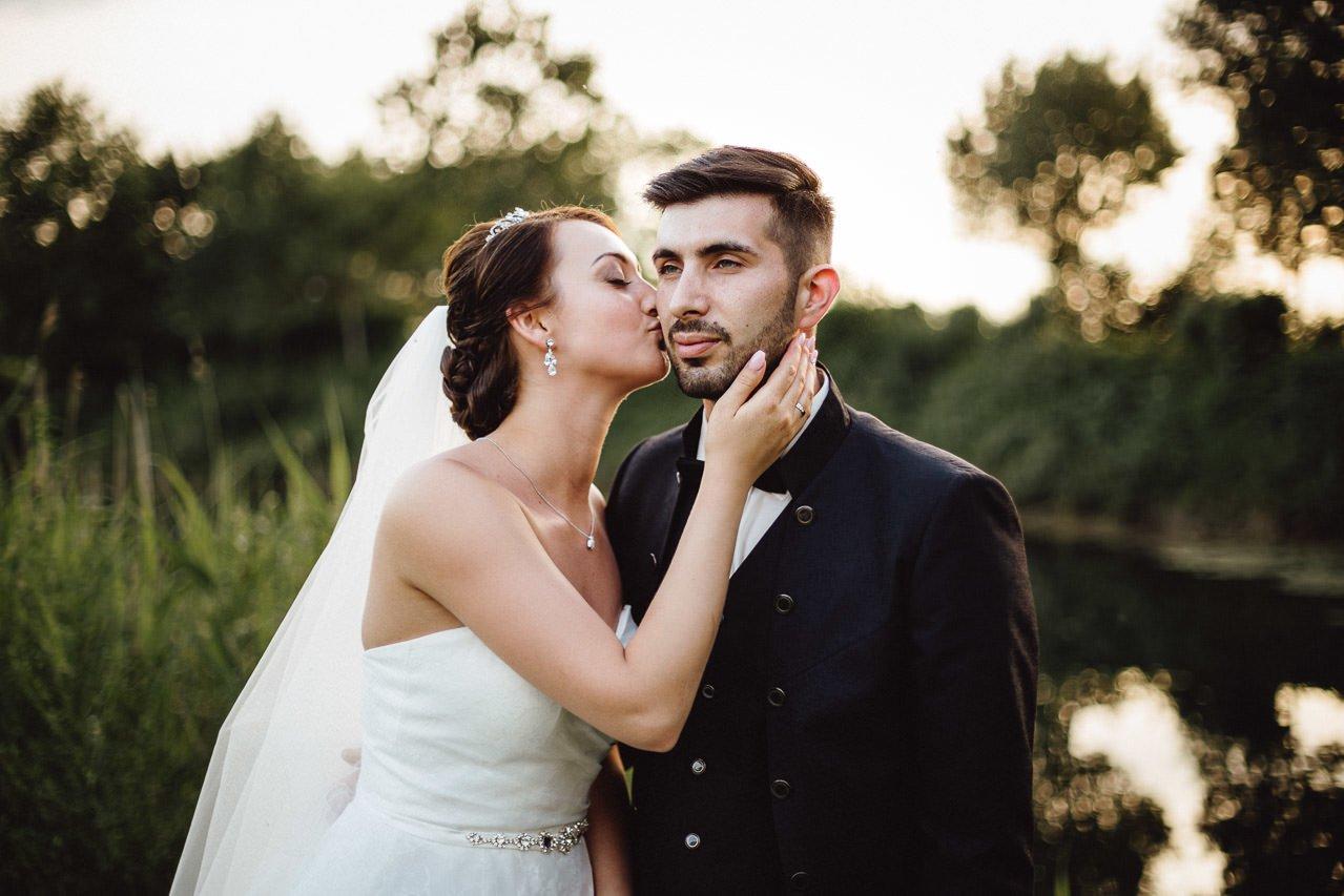Braut und Bräutigam küssen sich bei Sonnenuntergang im Garten des Hotels Darstein.