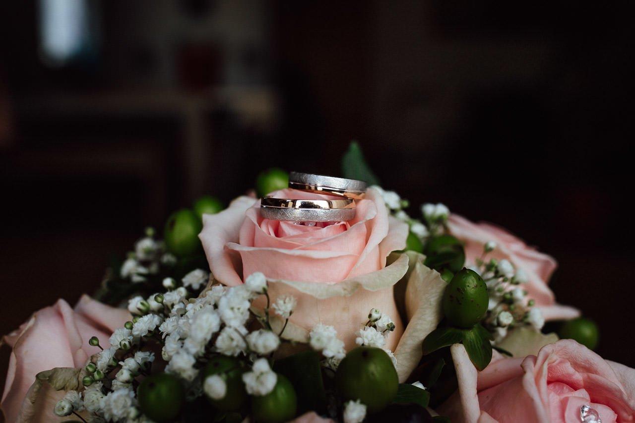 Eheringe liegen auf einem Brautstrauß aus Rosen.