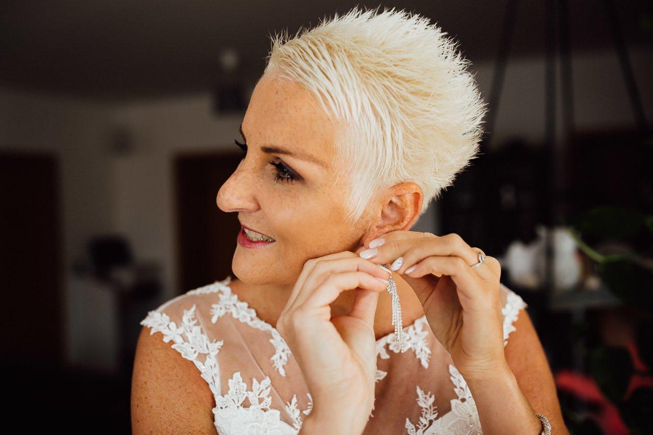 Die Braut mit weißem Haar steckt sich Ohrringe an.