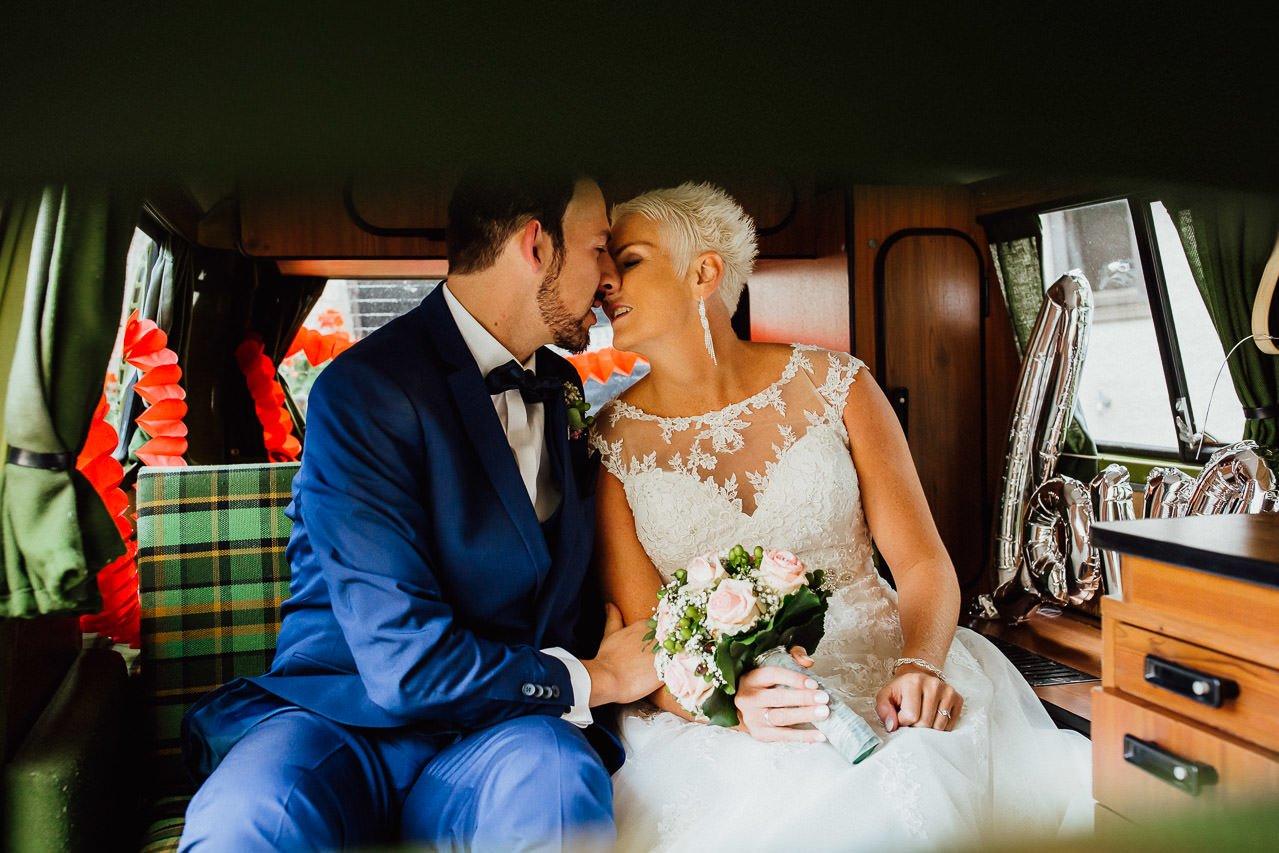 Küssen der Braut und des Bräutigams im Hochzeitsauto.