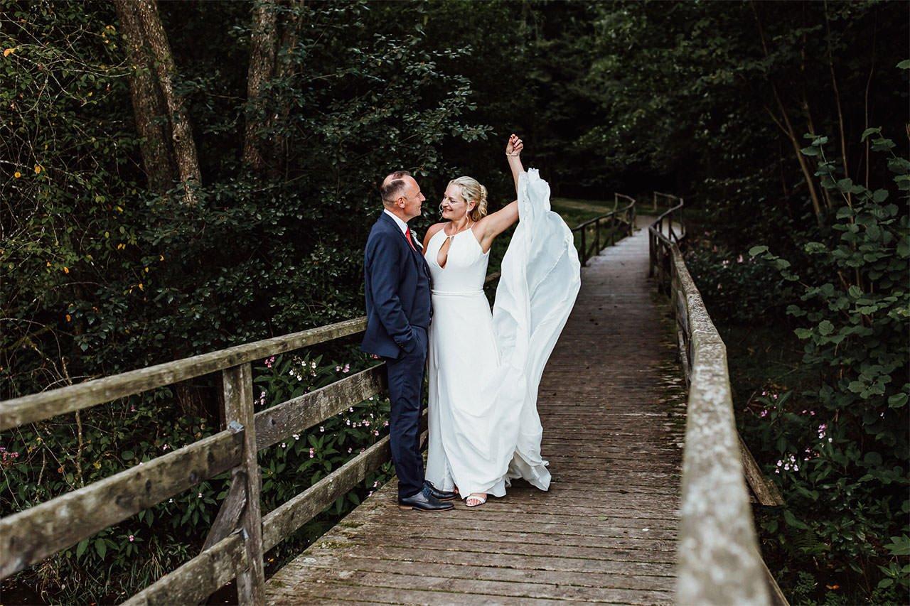 Braut schaut in die Augen des Bräutigams während Hochzeitsfotoshooting auf Holzbrücke im Wald