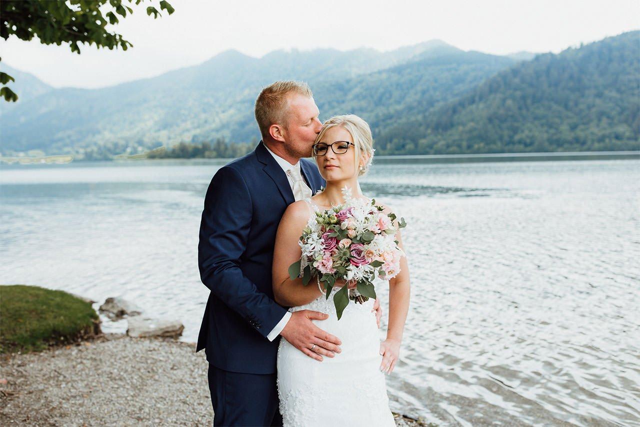 Ein Kuss vom Bräutigam während eines Hochzeitsfotoshootings am Schliersee