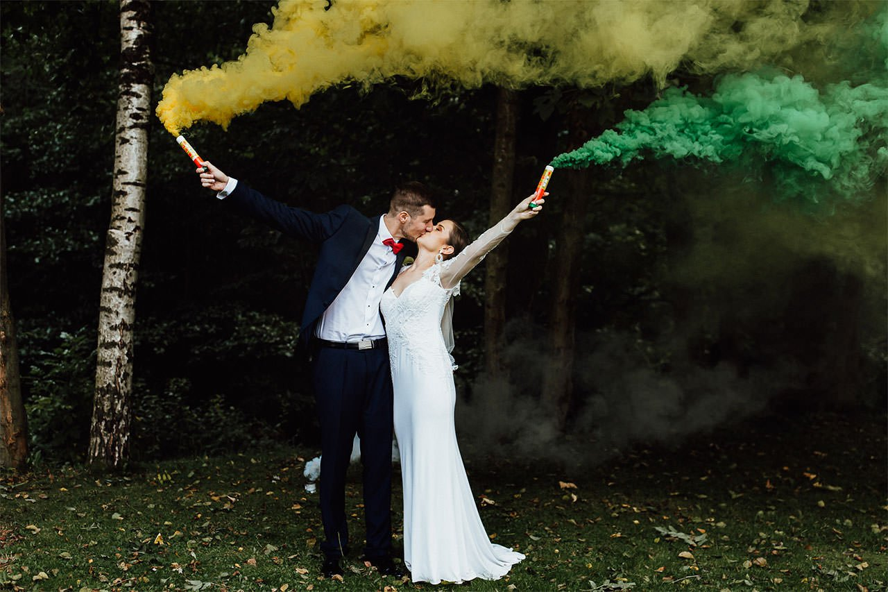 Braut und Bräutigam küssen während einer Hochzeitssession im Wald mit grünem und gelbem Rauchfackel.