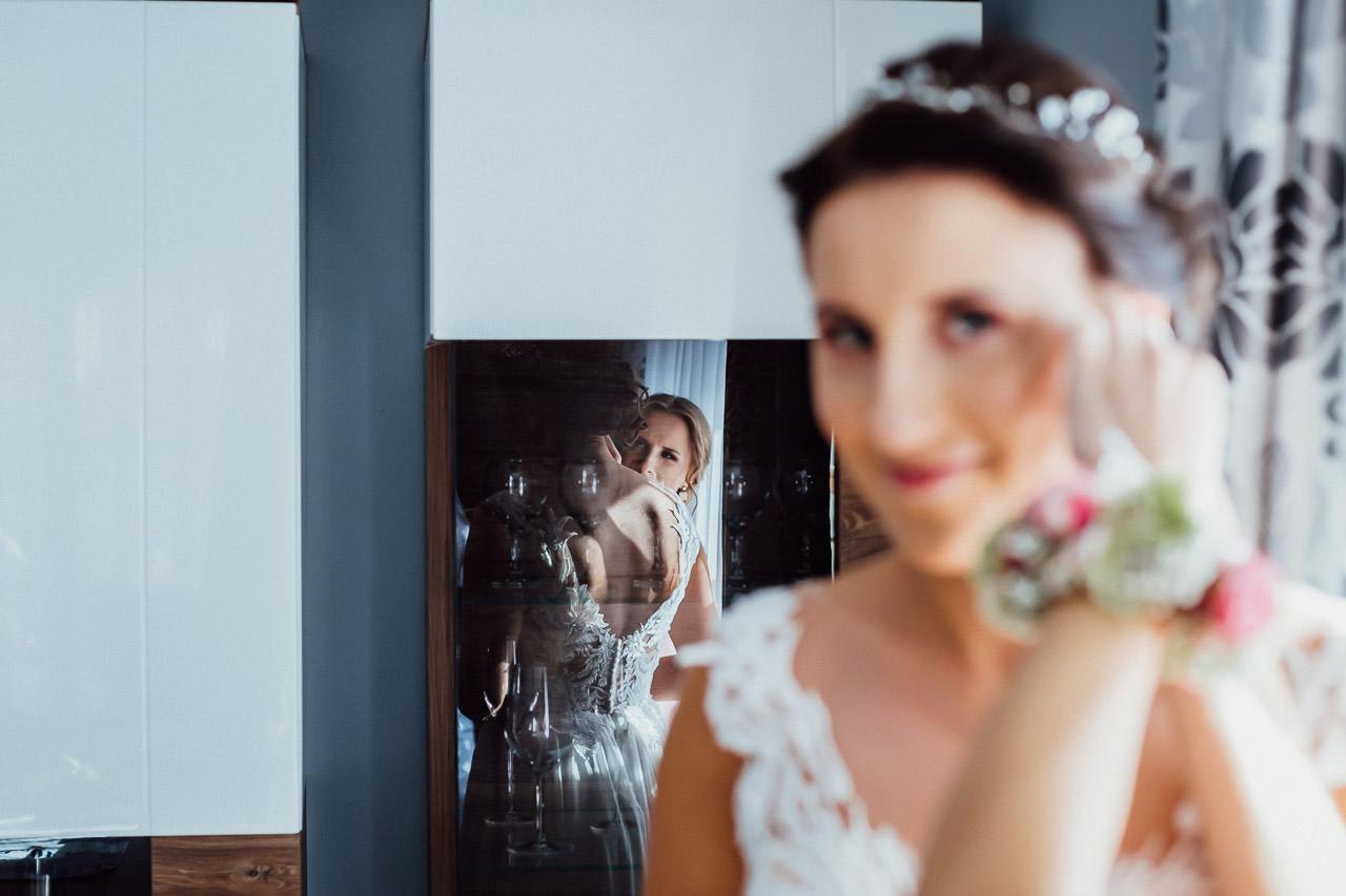 Vorbereitungen für die Hochzeit einer Braut, die Ohrringe umklammert. Trauzeugin hilft.
