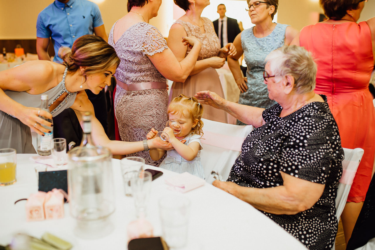 Ein Kind trinkt Wasser bei einer Hochzeit mit seiner unmittelbaren Familie.