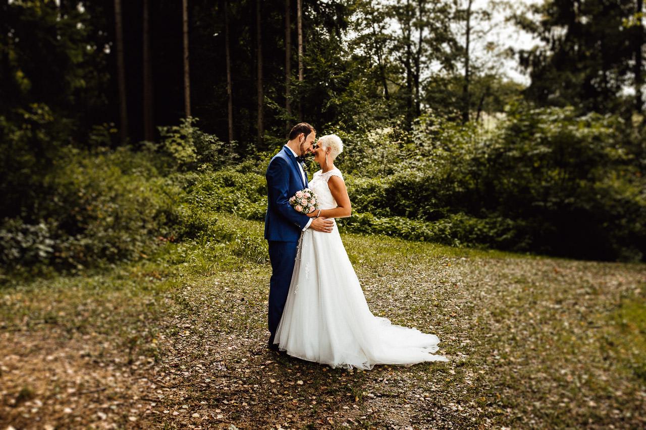 Die Braut mit ihrem Brautstrauß und der Bräutigam während eines Hochzeitsfotoshootings im Wald.