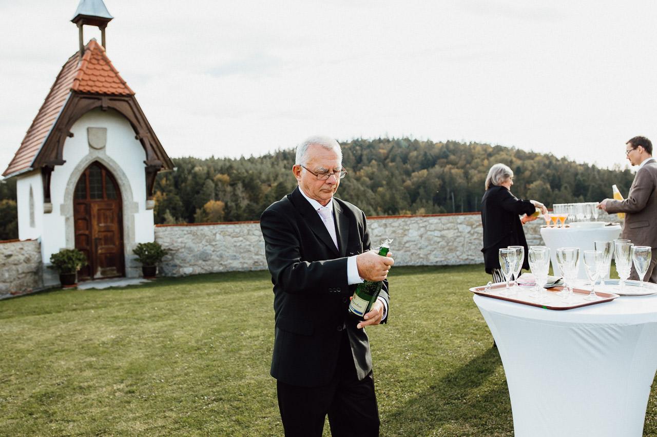 Der Vater der Braut öffnet nach der Trauung den Sekt.