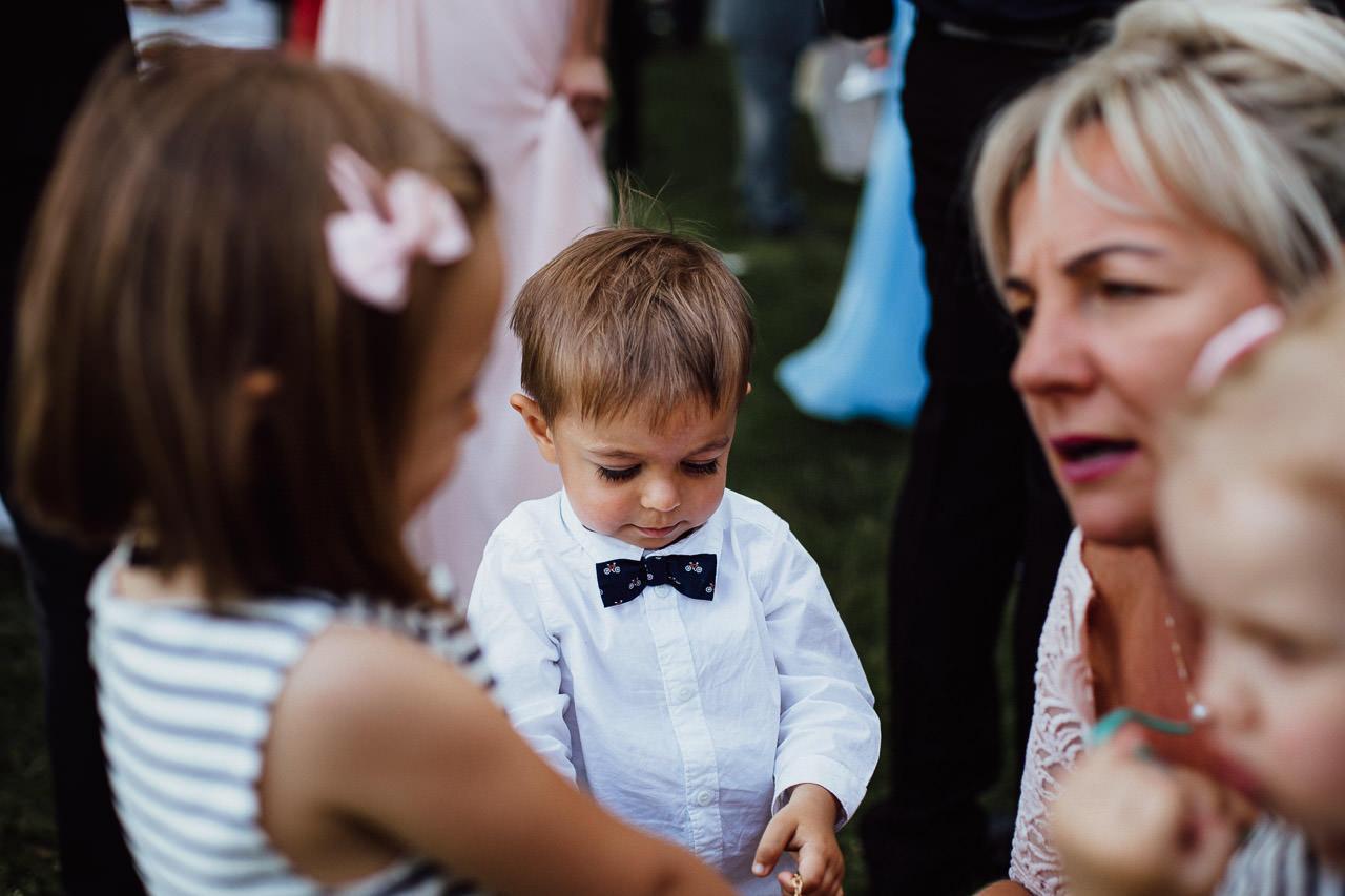 Ein kleiner Junge auf einer Hochzeit in einem eleganten Hemd und Fliege.
