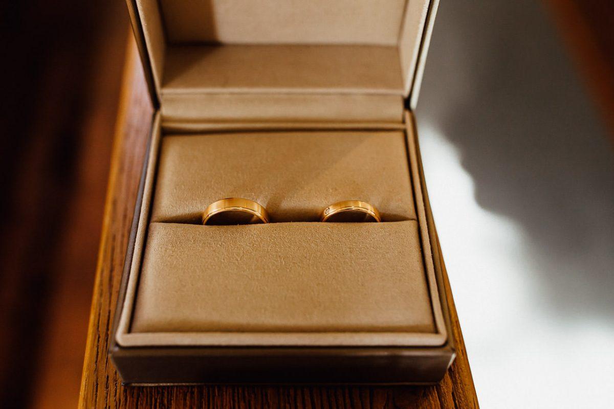 Elegante goldene Eheringe in einer Holzbox.