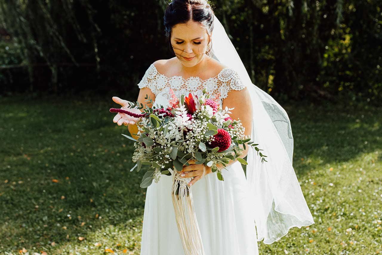 Eine Braut im Garten schaut über ihren Hochzeitsstrauß im Boho-Stil