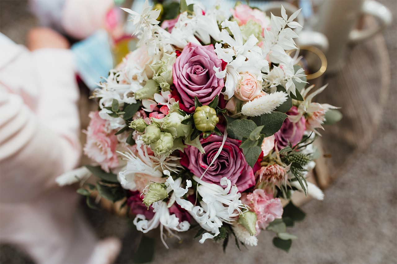 Die Blumen der Braut bestehen aus rosa Rosen.