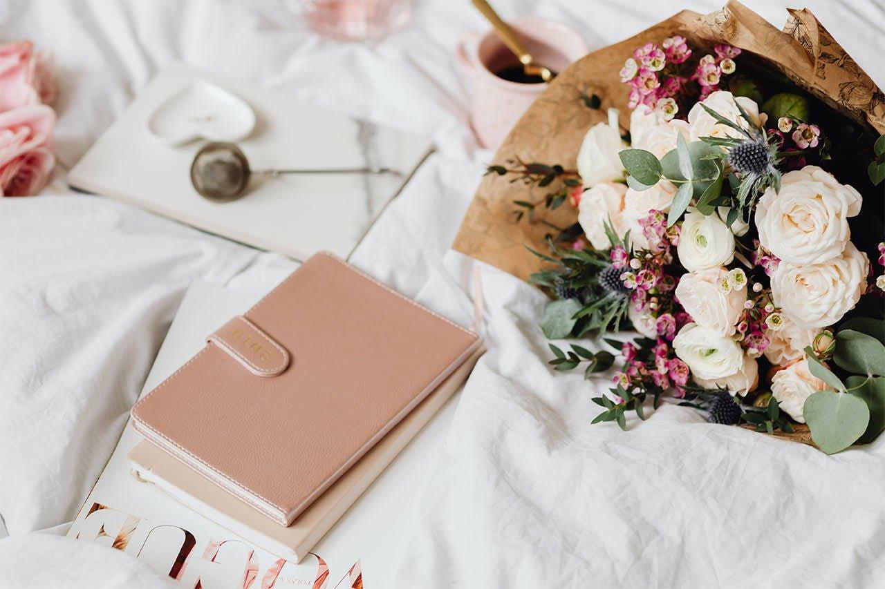 Notizbuch und Blumen bei der Planung der Coronavirus-Hochzeit
