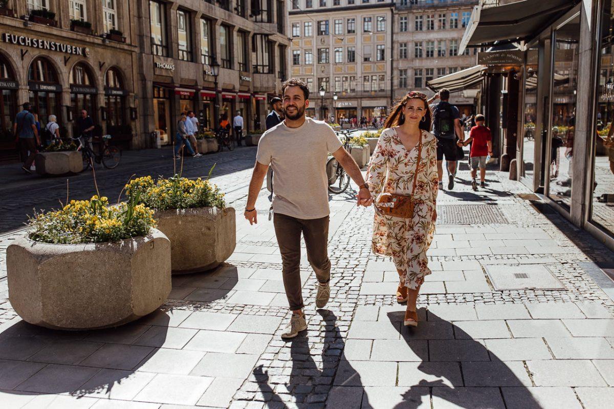 Das Paar spaziert händchenhaltend durch die Münchner Innenstadt.