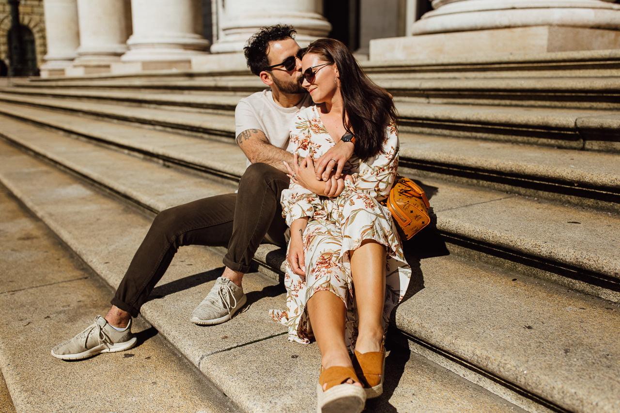 Bild des Paares in München auf der Treppe an einem sonnigen Tag.