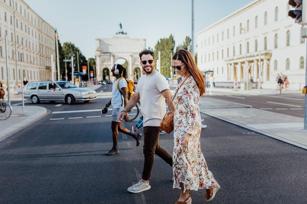 Ein Paar während eines Photoshootings in München überquert eine Straße in der Nähe des Siegestors