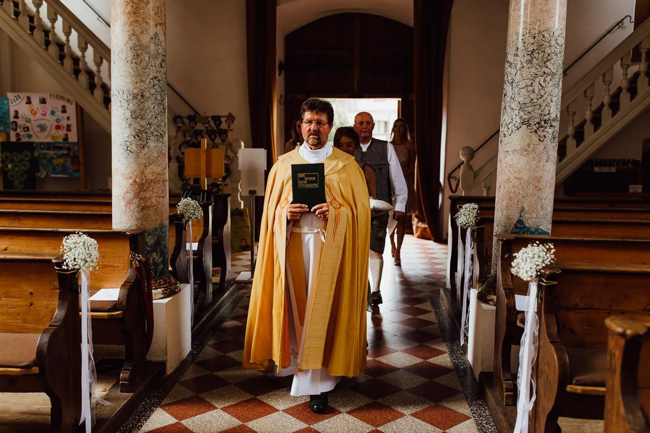 Der Pfarrer und die Braut mit ihrem Vater gehen zum Altar, wo der Bräutigam wartet