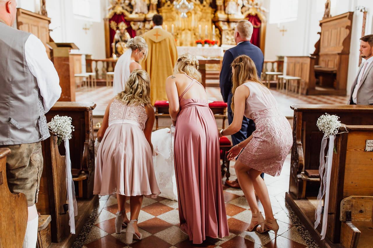 Bei einer kirchlichen Trauung in München helfen die Freunde der Braut, ihr Brautkleid auf dem Boden auszulegen.