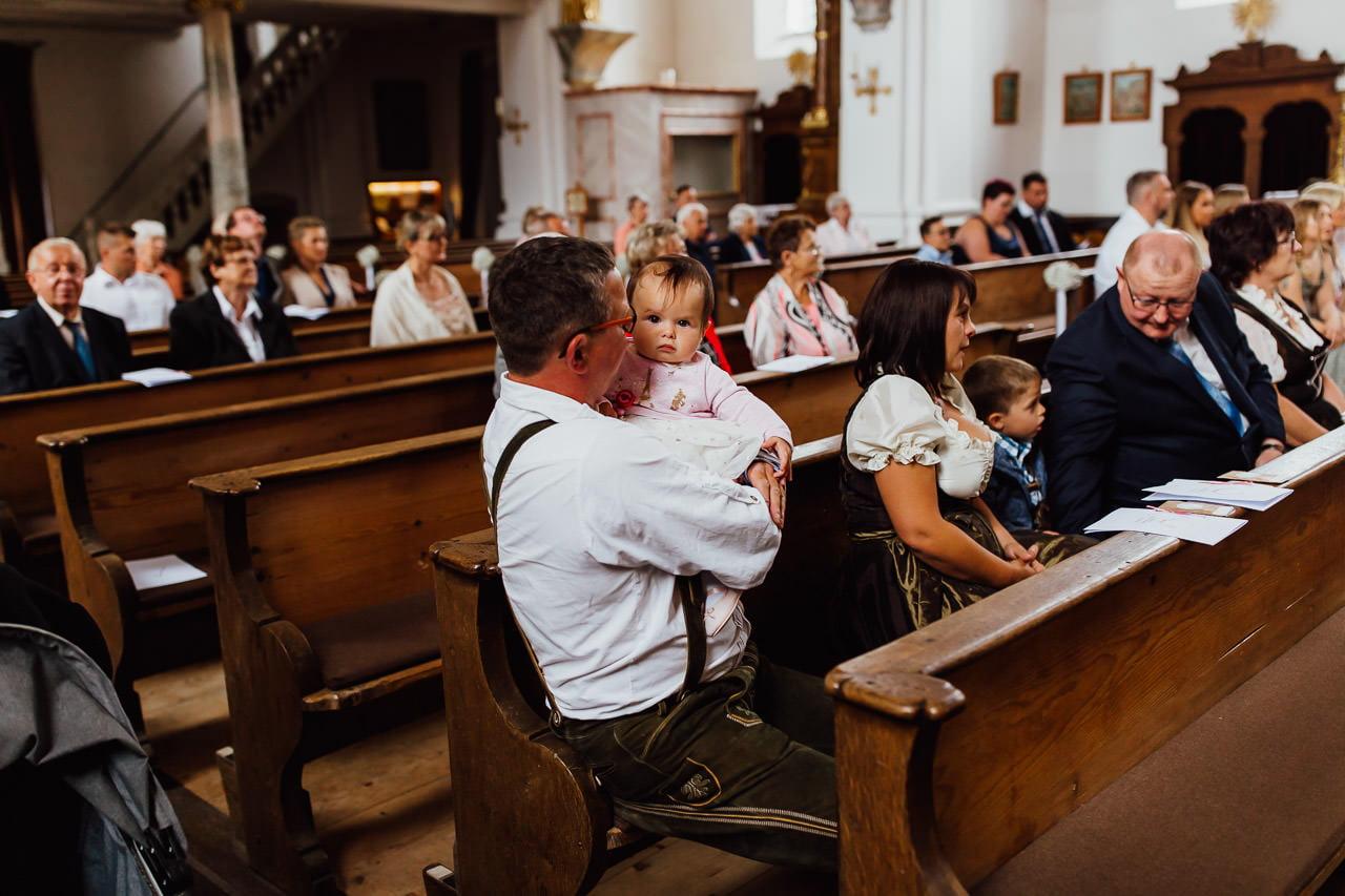 Gäste und ein kleines Kind bei einer kirchlichen Trauung in München