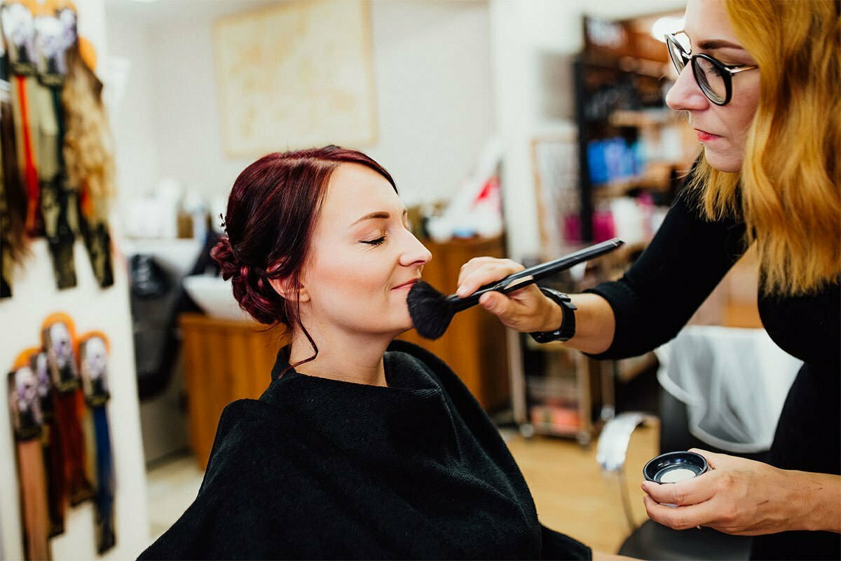 Braut beim Schminken im Kosmetiksalon