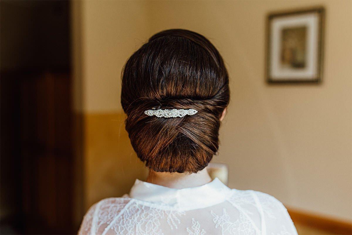 Das Haar der Braut mit einer schönen Haarnadel zu einem Dutt gebunden