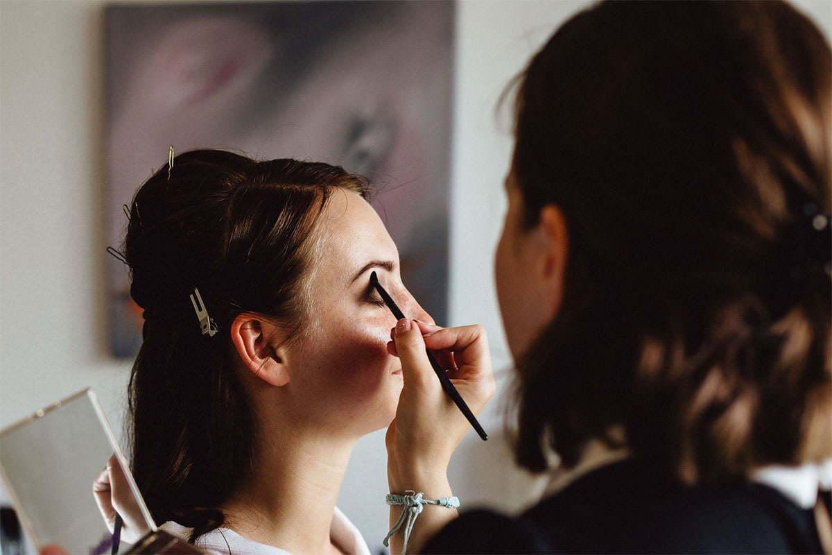 Die Visagistin malt die Augen der Braut mit einem Pinsel
