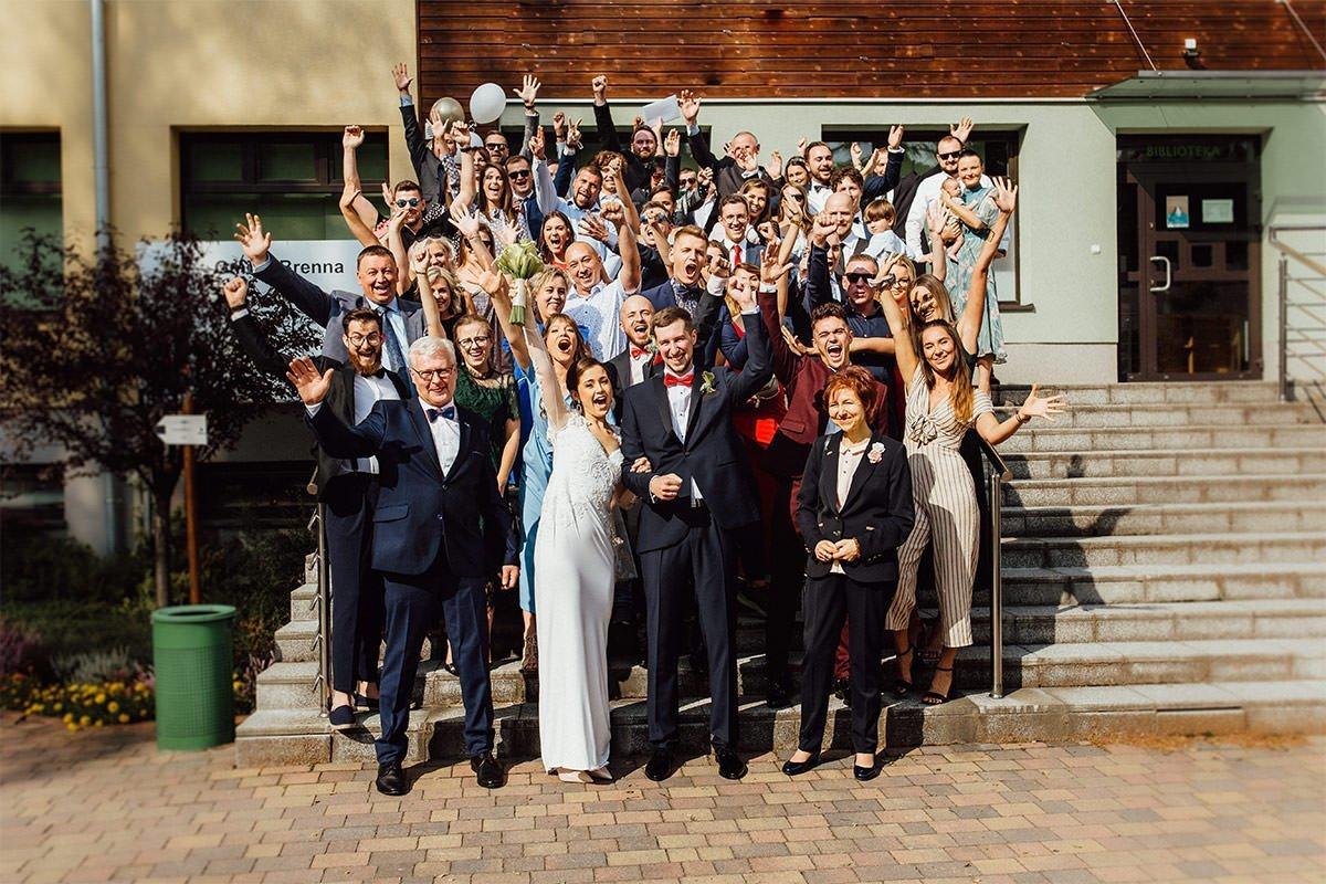 Während einer Hochzeit in Polen posiert die Familie für ein Gruppenfoto vor dem Rathaus von Brenna.