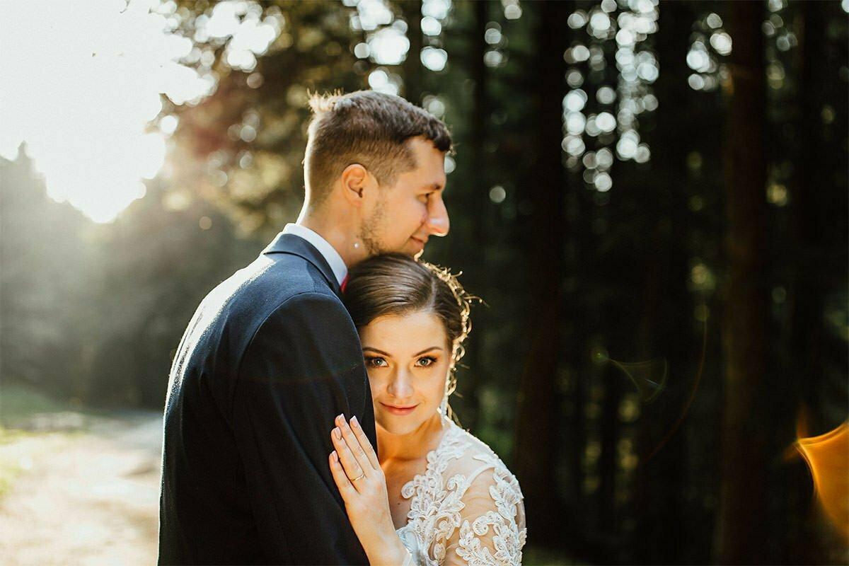 Die Braut und der Bräutigam posieren bei Sonnenuntergang für ein Foto im Wald.