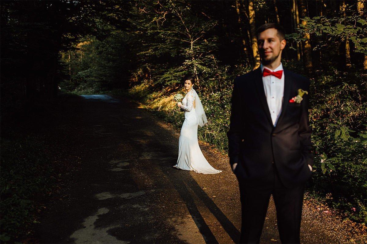 Braut blickt in Richtung des Bräutigams während eines Hochzeitsfotoshootings im Wald