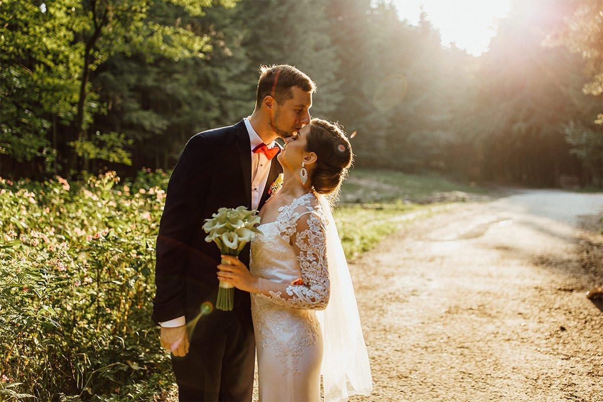 Der Bräutigam küsst die Braut auf die Stirn während eines Fotoshootings im Wald